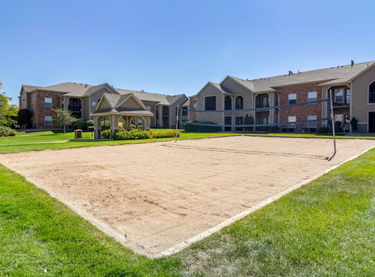 Sand Volleyball Court with Net  Srrounded by Grassy Courtyard with Building Exteriors in the Background