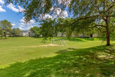 Large Grassy Courtyard with Trees Shrubs Bench  and Building Exteriors in the Background