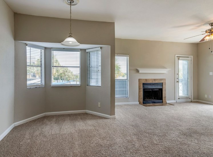 Vacant living room with carpet flooring, fireplace, and dining room area