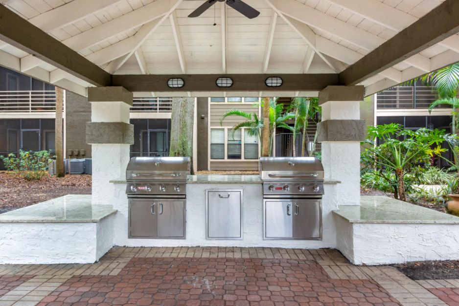 Covered Grill Station with 2 Grills with White Counters with Palm Trees and Building Exterior in the BAckground