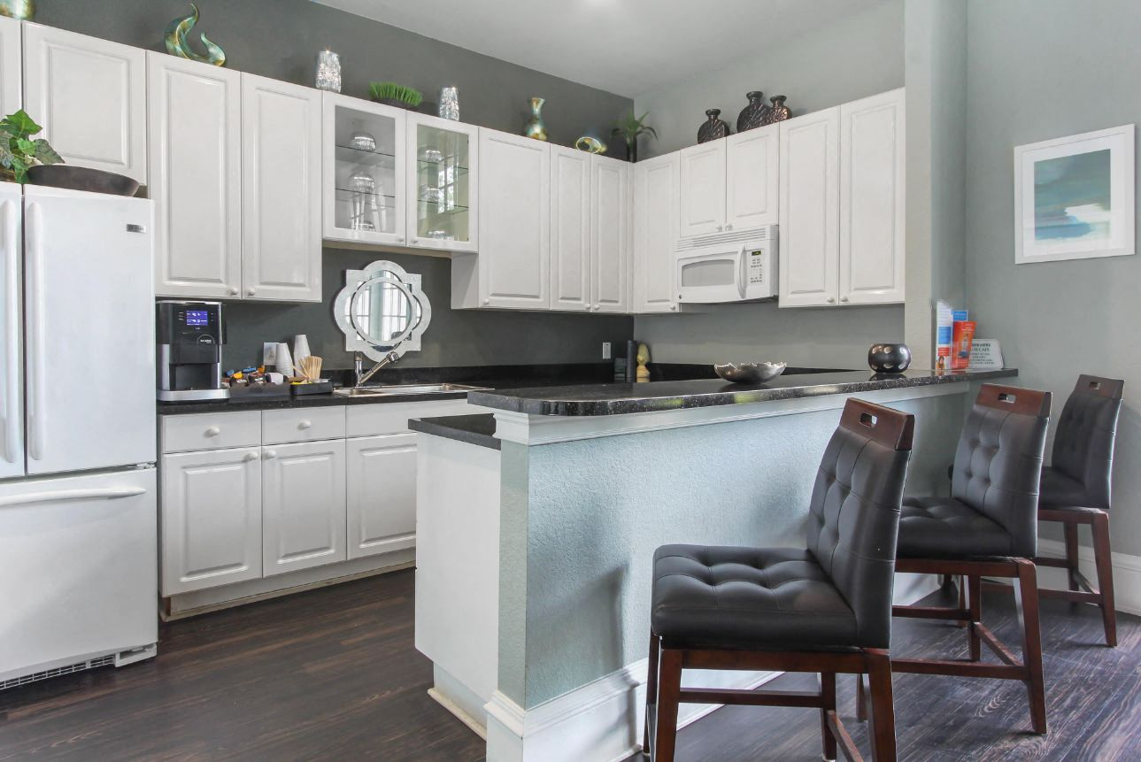 Decorated Clubhouse Kitchen with White Cabinets White Appliances with Black Counters and Brown Bar Stools