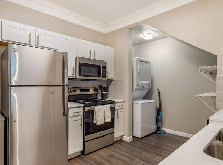 Model Kitchen with White Cabinets, Stainless Steel Appliances, White Counters with Decorations