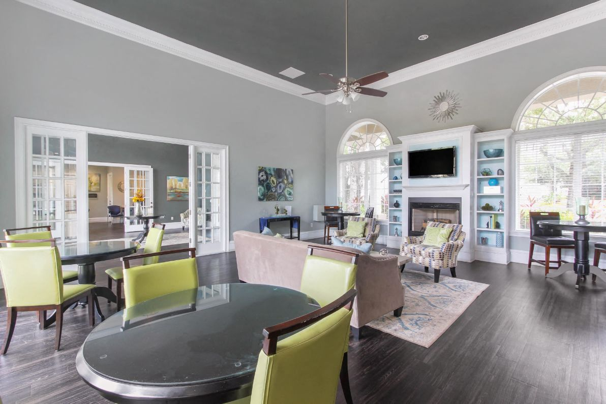 Clubhouse Seating Area with Large Windows on either side of Fireplace with TV and Shelves Surrounding Fireplace Multi Colored Accent Chairs Grey Couch and Dining Room Tables with Green Chairs and Clubhouse Foyer in the Background