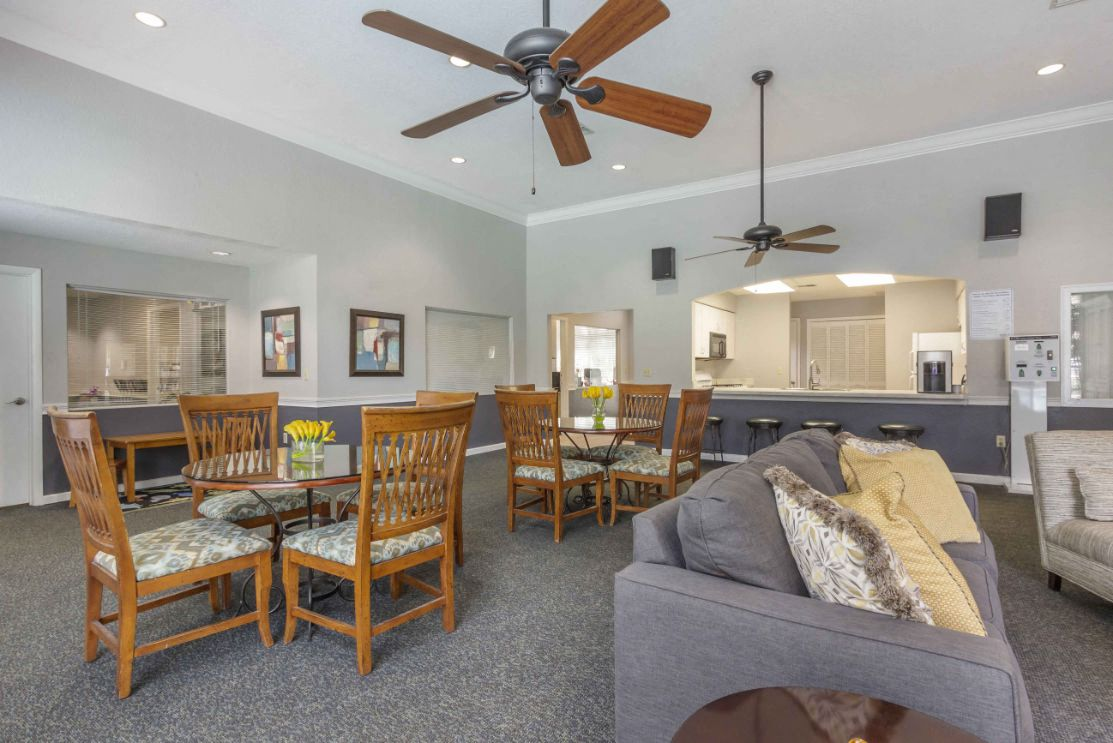 Clubhouse Seating Area with Dining Room Tables Behind Couch and Clubhouse Kitchen Bar with Barstools in the Background