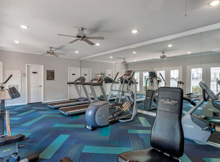 Fitness center with blue and teal carpet, ellipticals, and ceiling fans