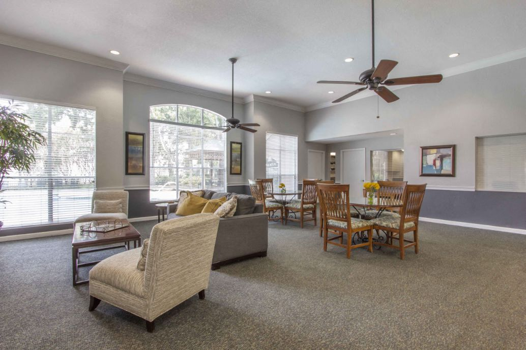 Clubhouse Seating Area with Dining Room Tables Behind Couch Cushioned Chairs and Coffee Table with Large Windows and Ceiling Fans