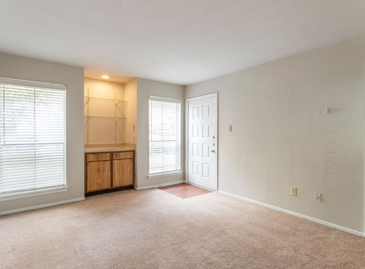 Living room with white walls, white trim, and wall to wall carpet