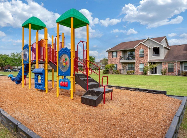 Colorful Playground  on Mulch with Building Exteriors in the Background
