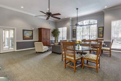 Clubhouse Seating Area with Dining Room Tables Behind Armoire Couch Cushioned Chairs and Coffee Table with Large Windows and Ceiling Fans