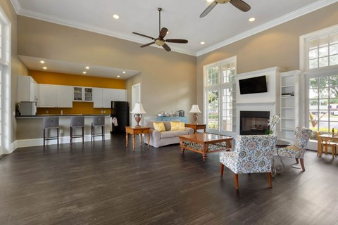 Clubhouse Seating Area with Large Windows Wood Coffee Table White Accent Chairs and  Fireplace with TV Mounted and Shelves Surrounding Fireplace and Clubhouse Kitchen with White Cabinets and Black Counters and Black Appliances