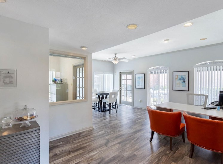 Clubhouse interior with hardwood style flooring, white walls, and two leather accent chairs