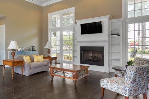Clubhouse Seating Area with Large Windows Wood Coffee Table White Accent Chairs and  Fireplace with TV Mounted and Shelves Surrounding Fireplace