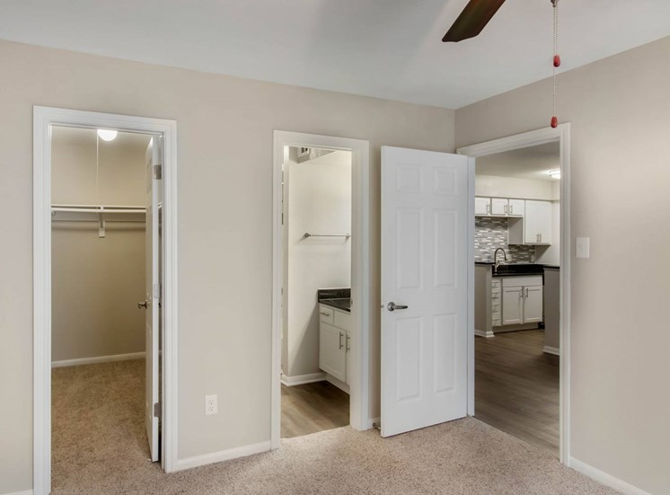 Carpet bedroom with en suite bathroom, two tone paint, ceiling fan and entrance to closet
