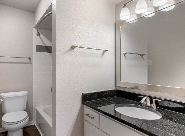Bathroom with granite countertops, toilet, white shower tiles in shower with bathtub and towel bars.