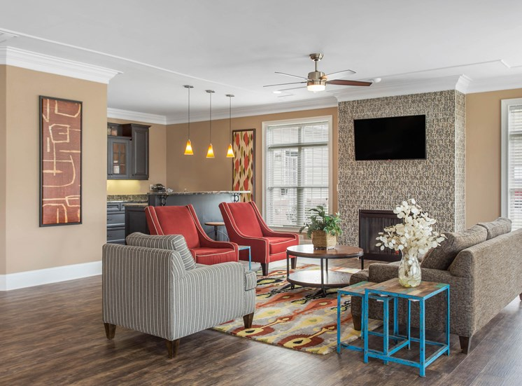 Clubhouse interior with gray sofas, two orange accent chairs, a mounted tv, blue side table, and hardwood style flooring