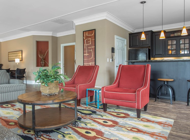 Clubhouse interior with two orange accent chairs, coffee table, orange and blue accent rug, and art mounted on the walls