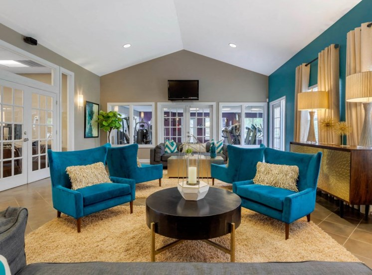 Clubhouse Seating  Area with Blue Armchairs Coffee Table Grey Couch and Blue Accent Wall with French Doors in the Background
