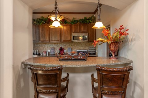 Clubhouse kitchen with breakfast bar area, two high top wooden chairs, coral flowers, and marble styled counter top