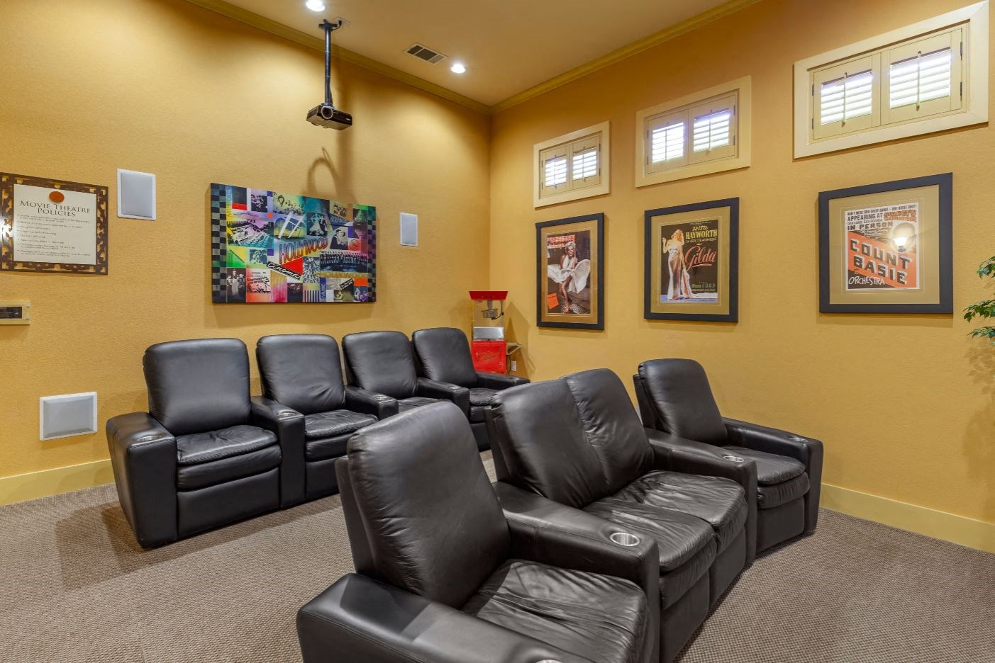 Movie theater with black leather recliners and decorative photos in the background.