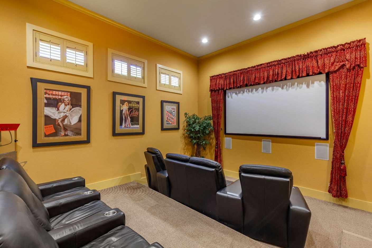 Theater room with black leather recliners and screen projector mounted on a yellow wall