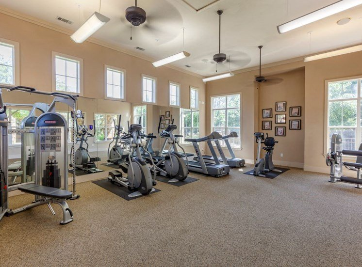 Fitness center with ceiling fans, gray carpet, ellipticals,  and stationary machines