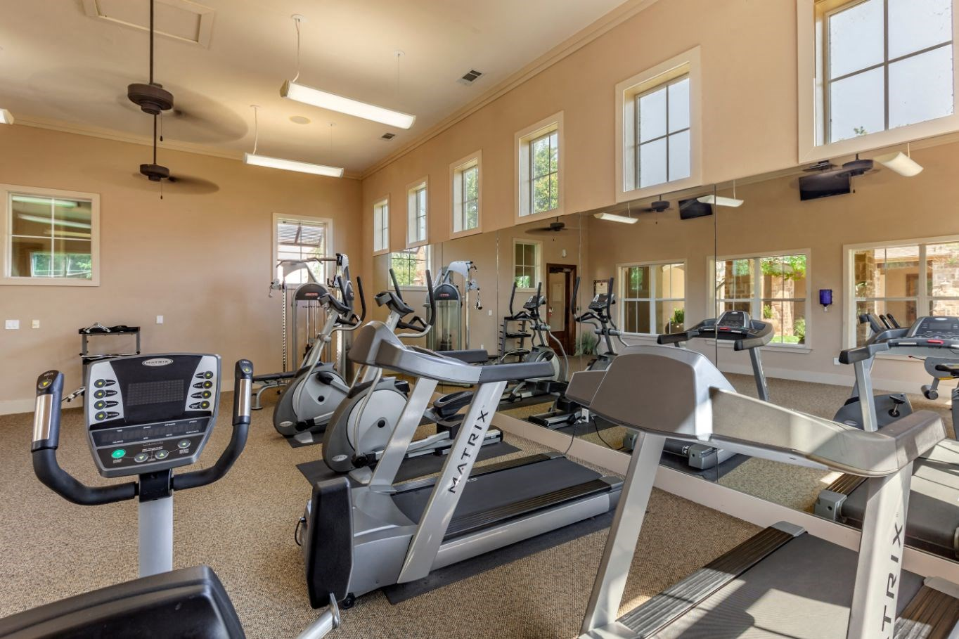 Fitness center with ceiling fans, treadmills, and stationary bikes with windows placed higher up on the walls.