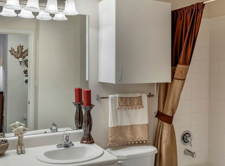 Bathroom with a cabinet located above the toilet, garden style bathtub, decorative shower curtain that is a shiny maroon and gold color, and five vanity lights above the sink.
