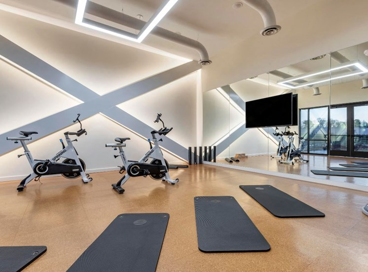 Fitness center with yoga mats mirror wall and a mounted television
