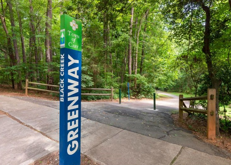 Entrance to Greenway Running Trail with Sign and Shaded by Tall Trees