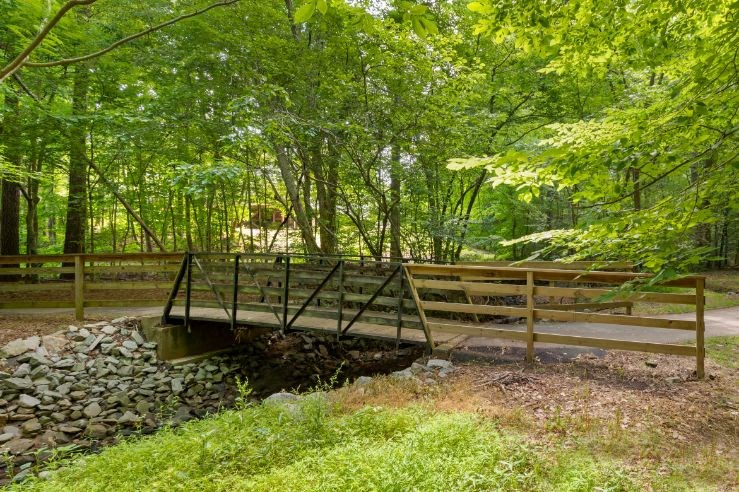 Walkway with Wood Bridge Over Creek with Stones Shaded by Trees