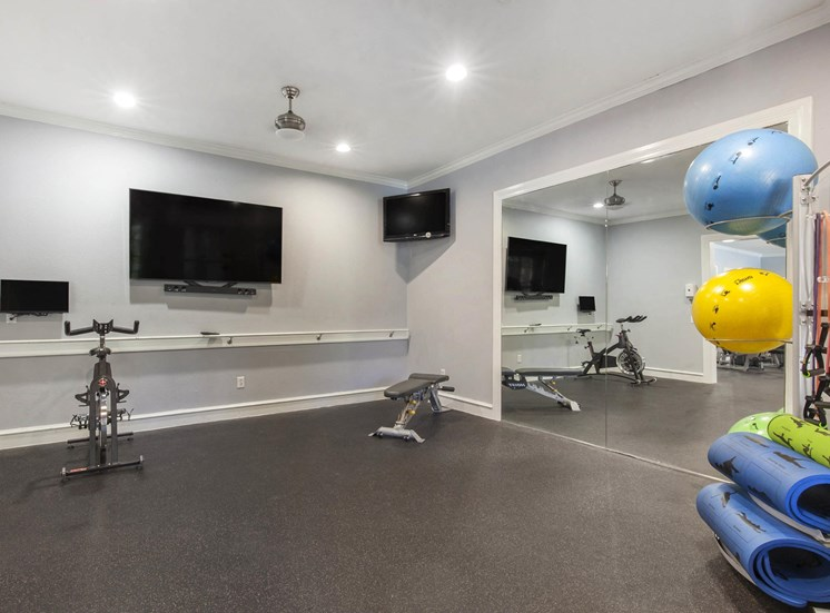 Fitness Center with Mounted TV, Exercise Equipment and Mirror Accent Wall