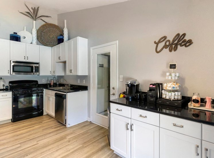 Clubhouse Kitchen with White Cabinets Black Counter Stainless Steel Appliances and Coffee Bar