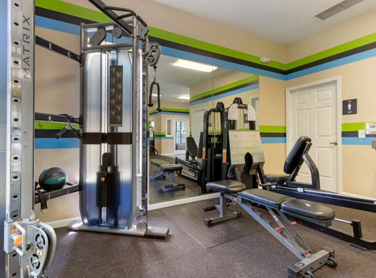 Fitness Center with Exercise Equipment Mirror Accent Wall and Green and Blue Stripes on the Wall