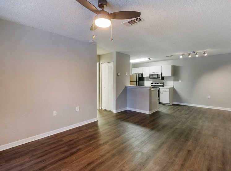Open Floor Plan with Breakfast Bar off Kitchen and Hardwood Style Flooring Throughout