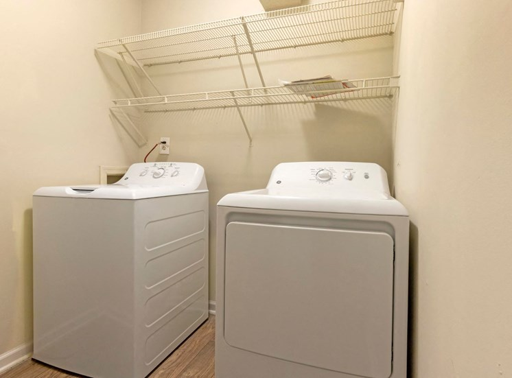 Washer and Dryer in Utility Closet Under Wire Shelf