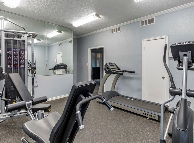 Fitness center complete with cardio and weight training equipment, gray walls, and large mirrors.