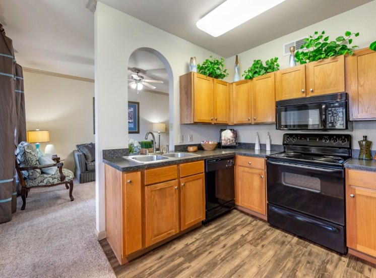 Model Kitchen with Black Appliances and Grey Counters and Wood Cabinets with Decorations