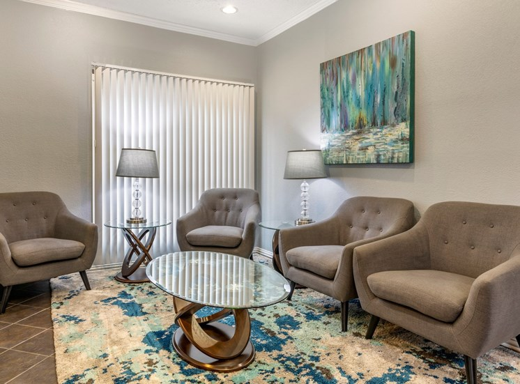 Seating area with beige tile floors, two-tone paint, modern beige side chairs arranged around an electric glass coffee table. Artwork hangs on the right of the room with beautiful colors of turquoise and blue hues. The room is completed with an abstract beige and turquoise area rug and chic glass side table lamps.