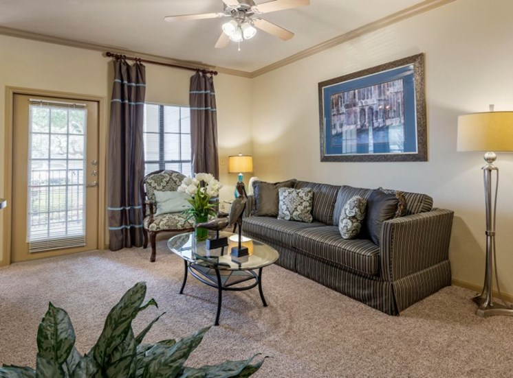 Furnished Model Living Room with Private Patio Access Couch Coffee Table and Plant