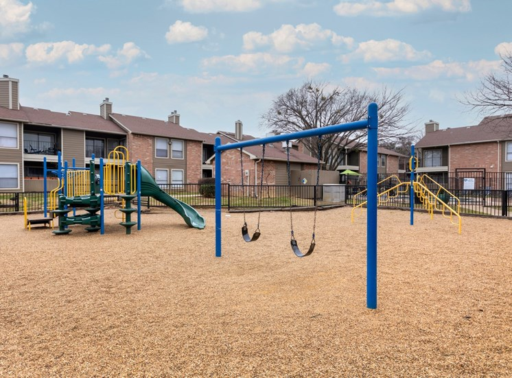 Large playground with swing-set, yellow jungle-gym, and a multi-activity play set green curved slide.