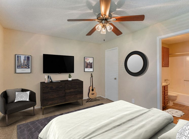 Decorated bedroom with ceiling fan mounted television en suite bathroom and an accent chair
