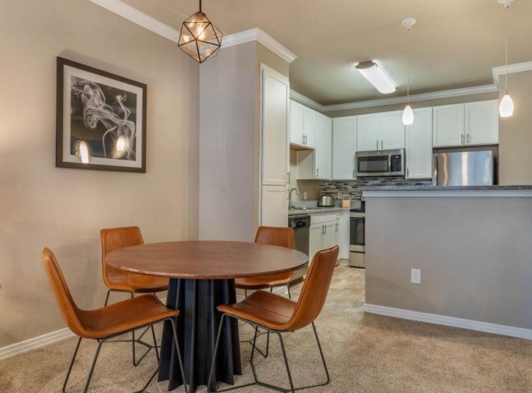 Dining Room with wooden kitchen table, kitchen chairs, mounted framed photos, and view of fully equipped kitchen
