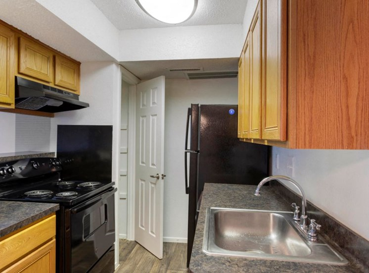 Fully equipped kitchen with wooden cabinetry and hardwood style flooring