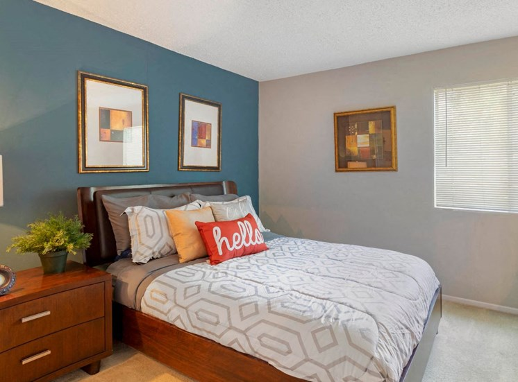 Furnished bedroom with blue accent wall, white bedding, framed photos, and wooden nightstand