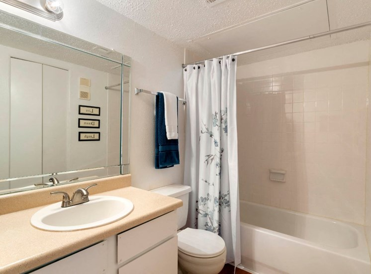 Bathroom with garden style bathtub, blue and white decorative towels, and a light gray shower curtain