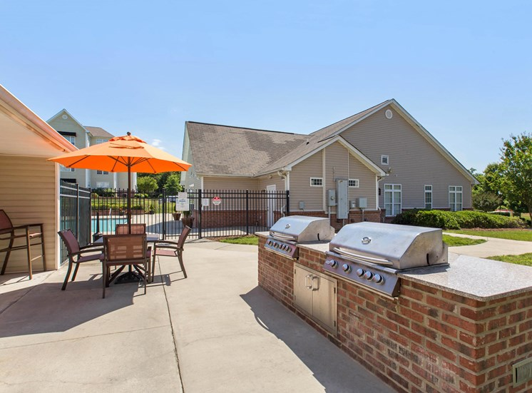 Poolside Summer Kitchen Grilling Area with Picnic Table with Orange Umbrella