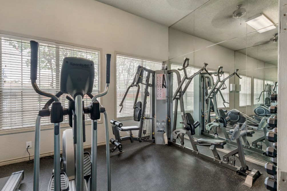 Fitness center with a mirrored wall and windows overlooking the scenery and an elliptical