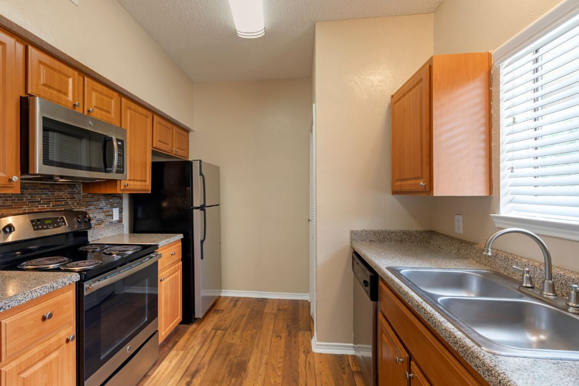 Fully Equipped kitchen with brushed nickle appliances double basin sink and hardwood style flooring
