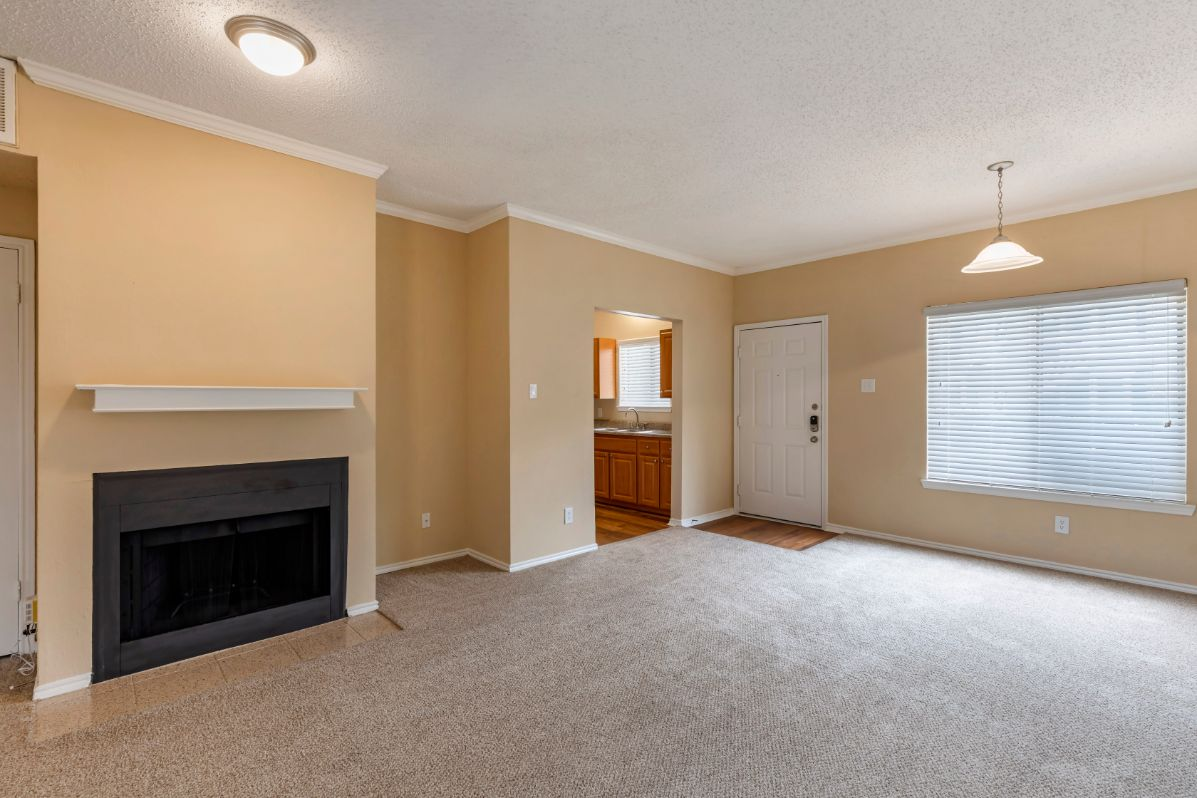 Living room with carpet peach colored walls white trim and a window. Living room is also adjacent to fully equipped kitchen.