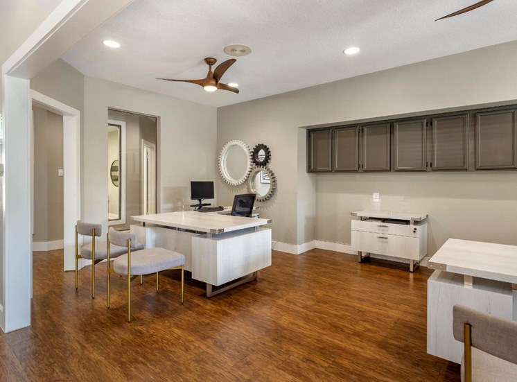 Leasing center with a white desk, chairs, hardwood style flooring, wooden style ceiling fans, and taupe cabinets along the wall